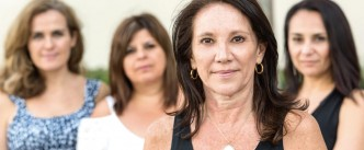 four hispanic or middle eastern mature women posing looking at the camera